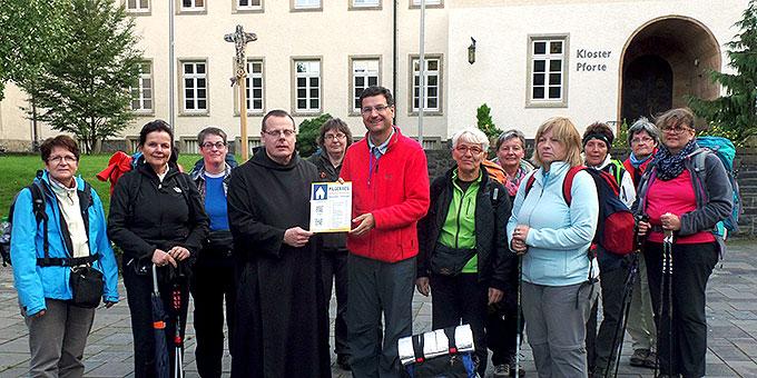 Prior P. Albert nimmt das Hinweisschild auf den neuen Pilgerweg entgegen (Foto: Herter)