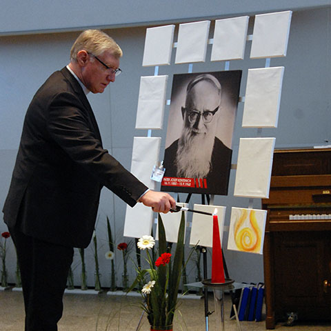 Pater Güthlein entzündet zum Start der Tagung eine Kerze beim Bild von Pater Josef Kentenich (Foto: Brehm)