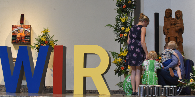 Eine Familie brachte stellvertretend für alle anwesenden Familien Blumensträuße zur Statue der Heiligen Familie (Foto: Kröper)