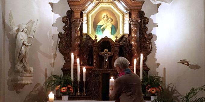 Die Kerze mit dem Heilig Geist Symbol leuchtet vor dem leeren Platz des Tabernakels (Foto: Callegari)