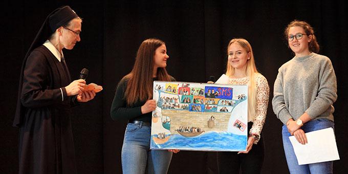 Die Schülervertretung überreicht einen Bildblock, für den jede Klasse ein Schiff gestaltet hat. Zur bleibenden Erinnerung sind die Schülerinnen als Schiffspassagiere dargestellt (Foto: Sch.Marienschule)