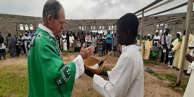 Pfarrer Alois Baumberger bei der Weihwassersegnung inmitten der Baustelle der neuen Wallfahrtskirche des Wallfahrtsortes Marza, Kamerun (Foto: privat)