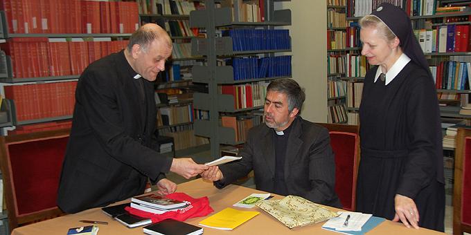 Schwester Gertrud-Maria Erhard und Pater Raul Espina überreichen Pater Bechina Informationsmaterial (Foto: Brehm)