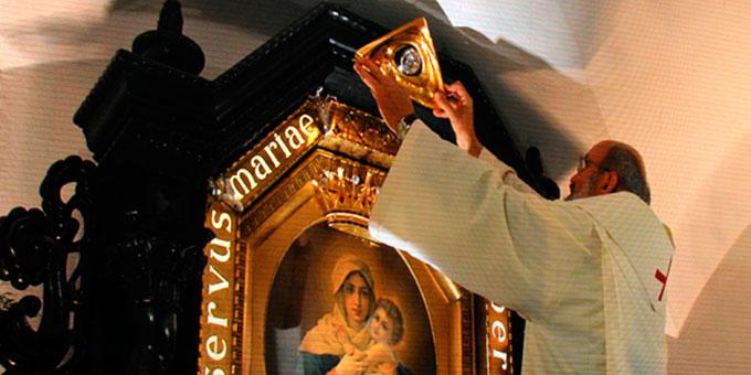 Das Gott-Vater-Symbol, ein Geschenk Pater Kentenichs für das Urheiligtum, wird von Pater Heinrich Walter über dem Gnadenbild befestigt (Foto: Kröper)