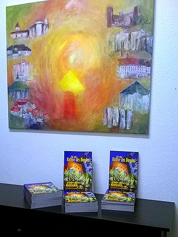 """Einige Exemplare der zweiten Auflage der Jubiläumsdokumentation vor dem ebenfalls zum Jubiläum entstandenen Gemälde """"Schönstattland"""" von Maria Kiess, Freising, das seinen Platz in der alten Goldschmiede, beim Büro des Leiters der Schönstatt-Bewegung Deutschland gefunden hat (Foto: Brehm)"""