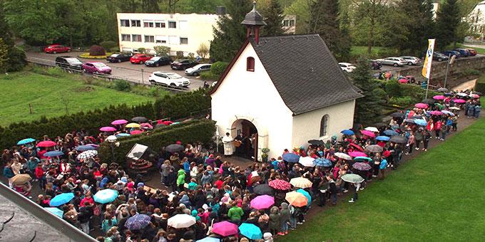 Auf dem Rückweg von der Pilgerkirche zur Schule machen alle trotz leichten Regens Station an der Gnadenkapelle  (Foto: Stienemeier)