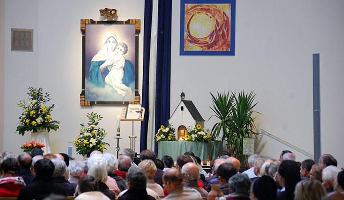 Ein Plakat macht das neue Pfingstfenster der Gründerkapelle in der Pilgerkirche präsent (Foto: Brehm)