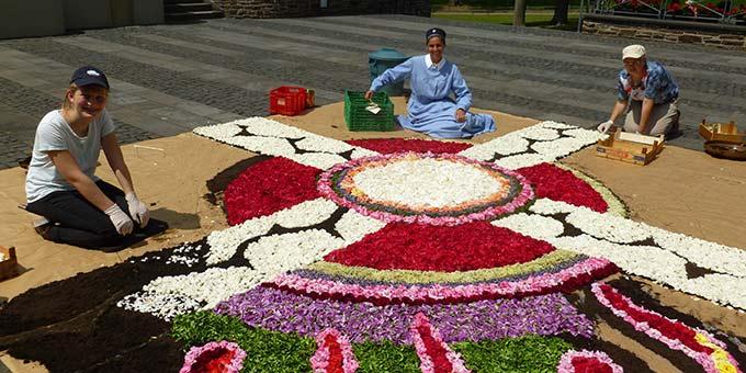 Auf der Trägerfläche aus Sand, Torf oder Sägemehl werden Tausende Blüten ausgelegt um die sprechenden Symbolteppiche zu gestalten (Foto: Schw. M. Joséfa Klein)