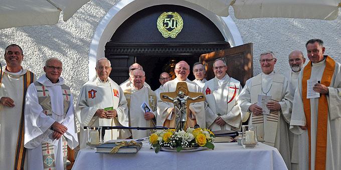 Hauptzelebrant Pfr. Heinz-Martin Zipfel hinter dem Kreuz der Einheit mit allen Konzelebranten des Festgottesdienstes (Foto: Baumann)