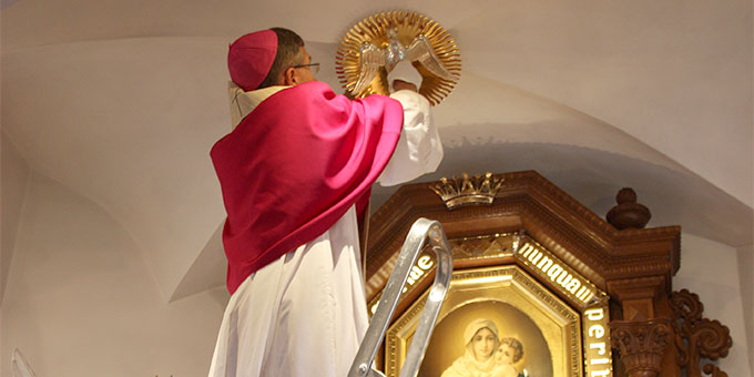 Bischof Gerber bringt das Heilig-Geist-Symbol neu an (Foto: Poppe)